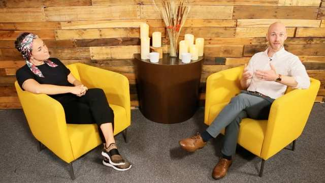 two people sitting on yellow chairs and talking